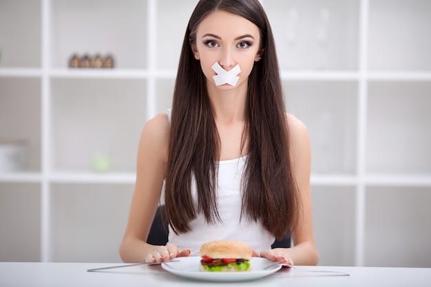 ダイエット。女性はジャンクフードを食べることを拒否します。健康的な食事とアクティブなライフスタイルのコンセプト