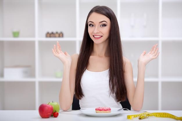 Концепция диеты. молодая женщина выбирает между фруктами и сладостями