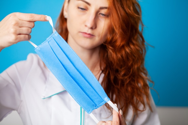 青色の背景にウイルスから保護するために口と鼻を覆うマスクを保持している女性