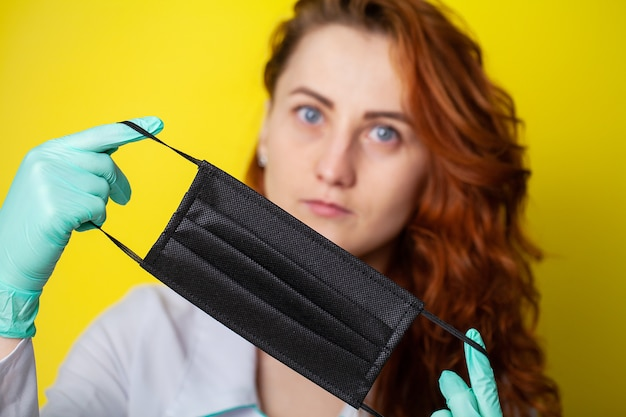 黄色の背景にウイルスから保護するために口と鼻を覆うマスクを保持している女性。
