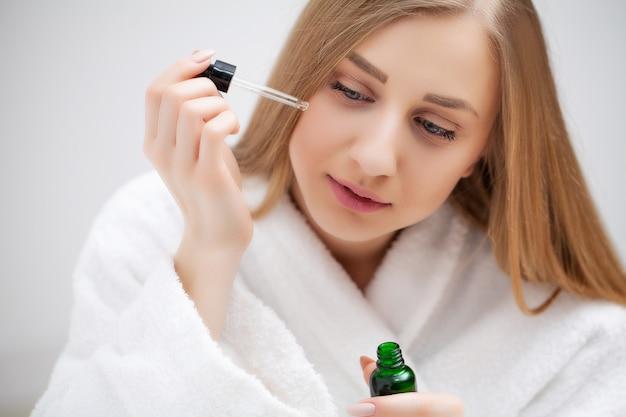 Женщина готовится к работе, делать утренний макияж в ванной комнате зеркало дома.