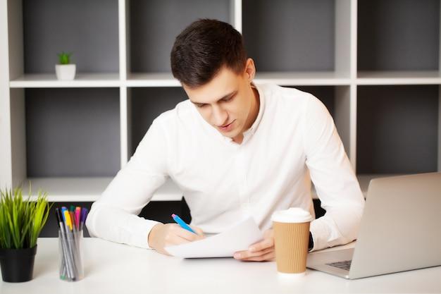 Успешный бизнесмен работает в офисе за ноутбуком