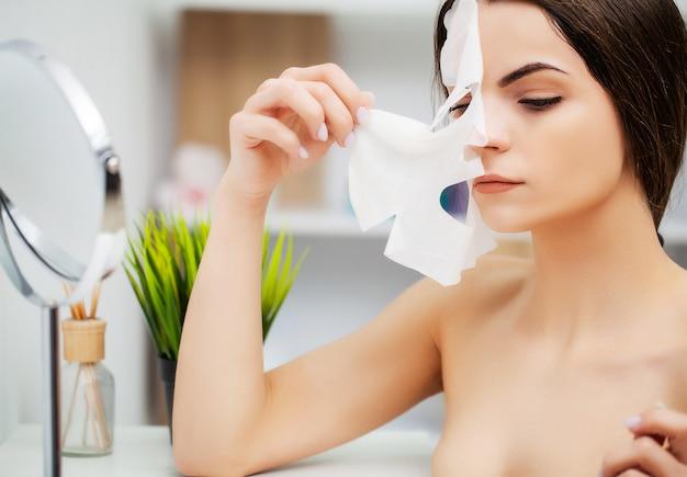 バスルームでの顔のマスクを持つかなり若い女性