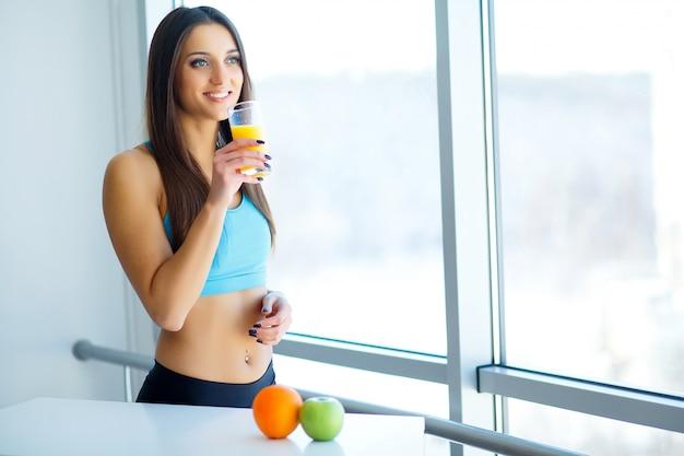 ダイエット。キッチンでオレンジのスムージーを飲むフィットネス若い女性へのクローズアップ