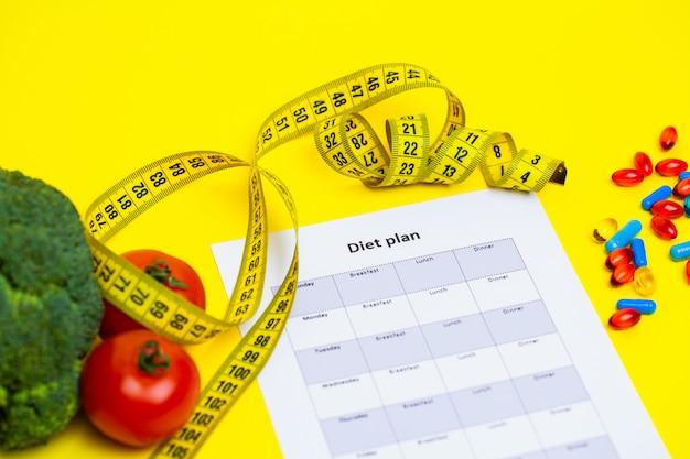 黄色の減量の丸薬と新鮮な野菜の食事療法の計画。