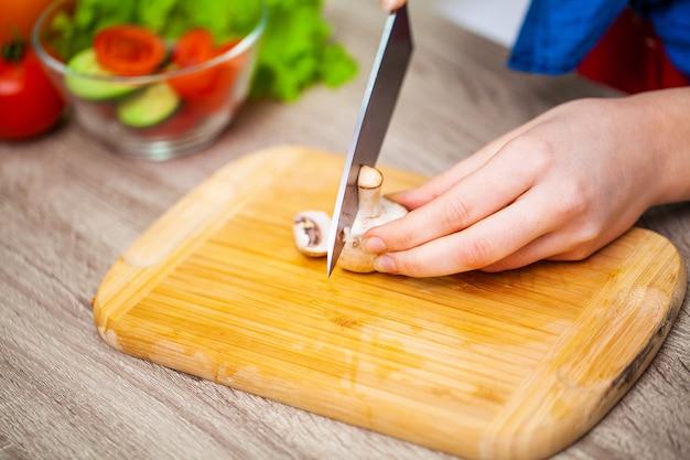 女性のクローズアップは、新鮮なサラダのキノコをスライスします。