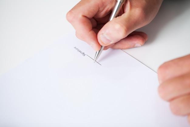 契約書に署名のオフィスの机に座っているビジネスマン