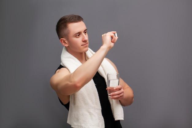 男はトレーニング後にアミノ酸の錠剤を服用します。