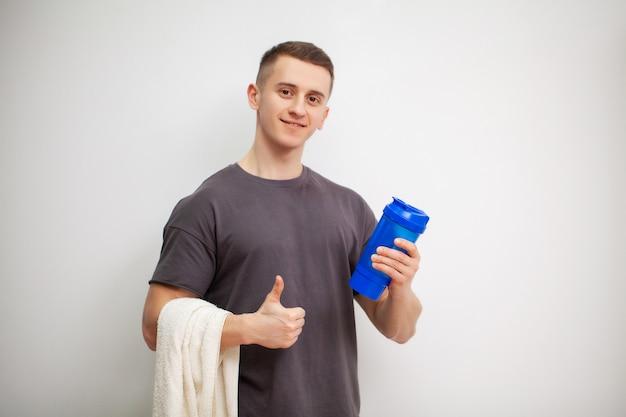 男は、トレーニング後にシェーカーでプロテインシェイクを準備します。