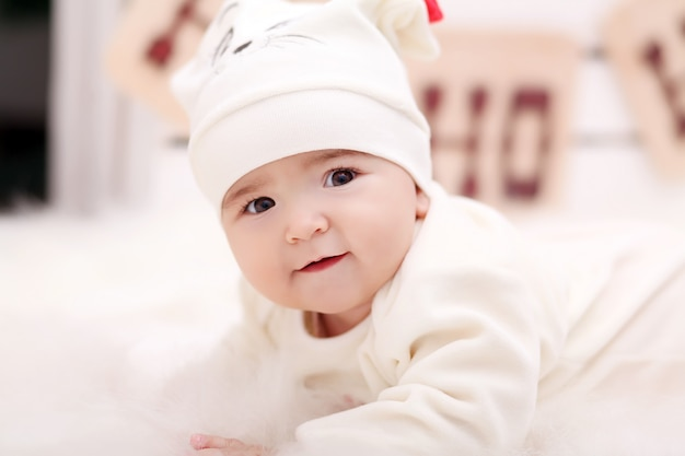 Девочка в шапке деда мороза с подарками под елку