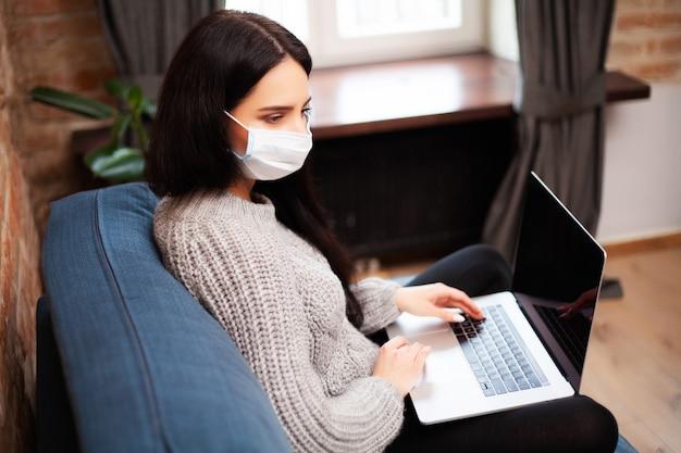 世界中でウイルスが蔓延している最中に、防護マスクを着た女性がラップトップで自宅で仕事をしている