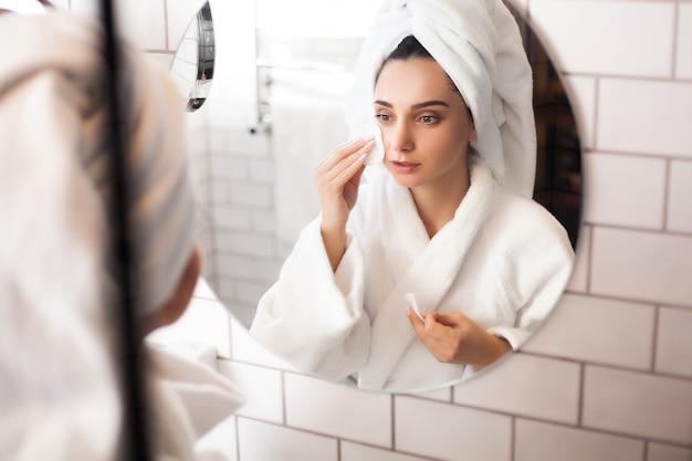 彼女の頭にタオルが付いているバスルームの女性は彼女の顔に化粧を適用します