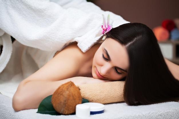 若い女性は美容スタジオでスパトリートメント中にリラックスします。