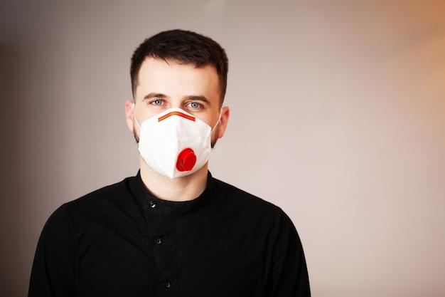 コロナウイルスからの保護のためのマスクを着てオフィスで働く男