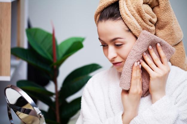 Милая женщина вытирает лицо полотенцем после принятия душа