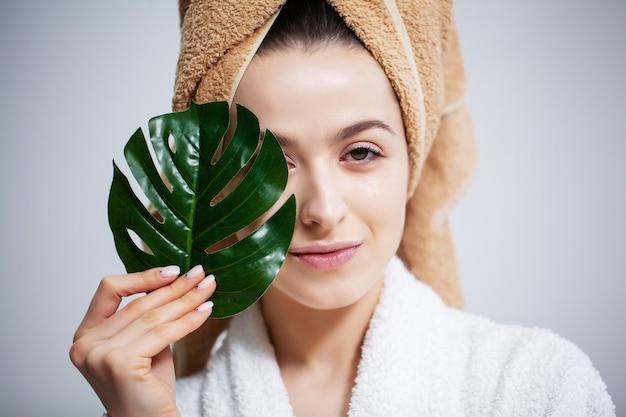彼の頭にタオルとシャワーを浴びた後緑の葉を持つかわいい女性