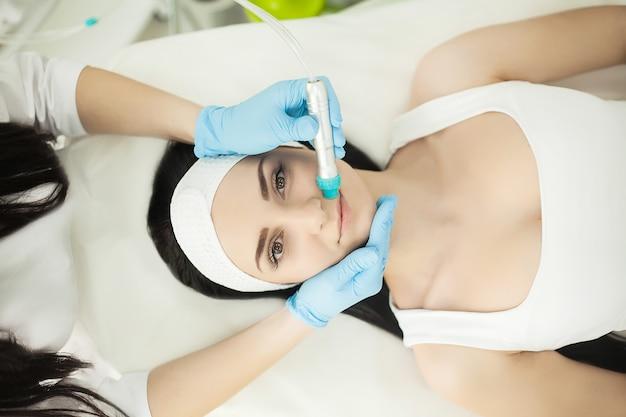 現在の治療法を使用して皮膚療法を楽しんでいる美容スパで横になっている女の子