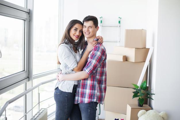 面白い若いカップルを楽しんで、新しい家への移動を祝います。
