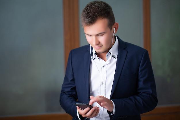 Красивый молодой работник использует телефон в офисе компании