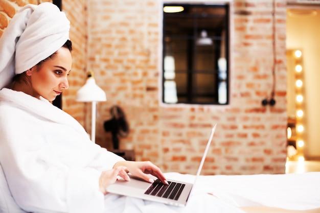 Красивая женщина сидит дома и работает на ноутбуке онлайн