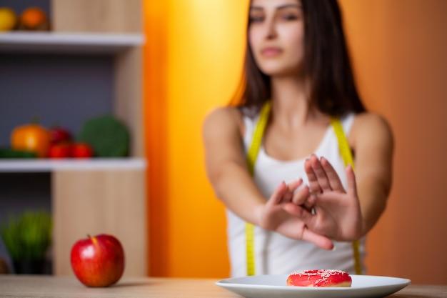 有用な食品と有害な食品を選択する美しい女性