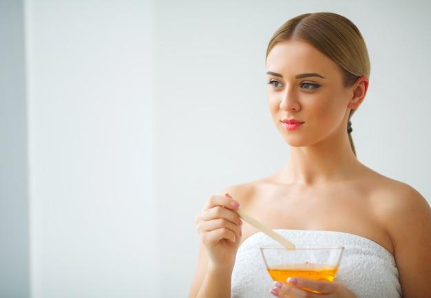 女性はオレンジ色のパラフィンワックスボウルを持ちます。ビューティーサロンの女