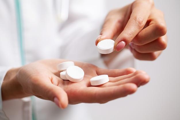 医師は、減量のための白い錠剤を保持する間近