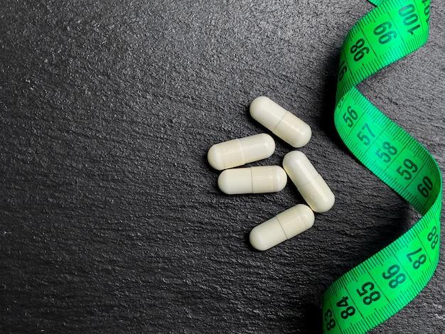 Белые таблетки для похудения рядом с рулеткой