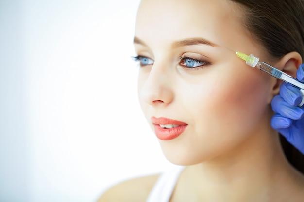 美容とケア美しい顔を持つ若い女性の肖像画。美容師が注射をします。高解像度