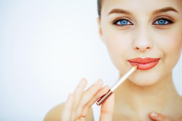 美容とケア美しい肌を持つ若い女性の肖像画。美しい唇。彼女の手で口紅を持つ女の子。美しい青い目を持つ女性。化粧。唇のケア