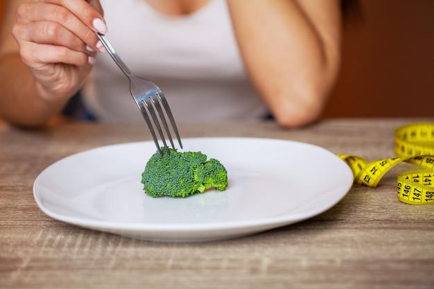 Девочка ест диету брокколи для похудения