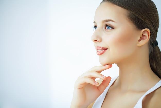 美容とケア美しい肌を持つ若い女性の肖像画。美しい唇。女の子は唇の世話をします。美しい青い目を持つ女性。化粧。リップスクラブピーリング