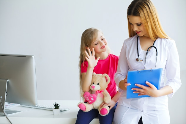 ハンサムな医者が聴診器で小さな女の子を調べる