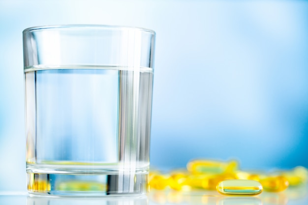 Витамины и рыбий жир в желтых капсулах со стаканом воды