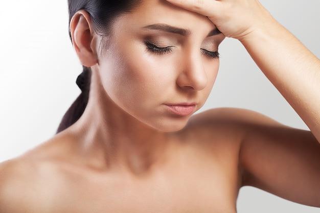 若い女性は彼女の頭のひどい痛みに苦しんでいます