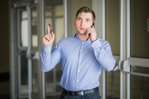 Веселый человек в офисе, отвечая на телефонные звонки