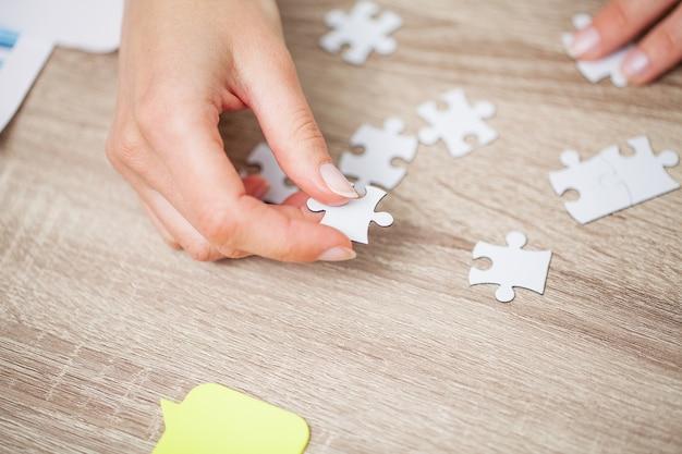 ビジネスコンセプト、女性の手が会社の成功を象徴するパズルを作る