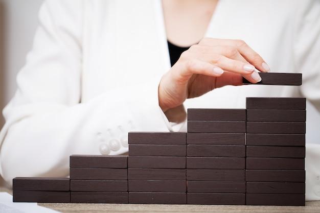 ビジネスコンセプトは、女性の手が会社の成功を象徴する木製の立方体を作る