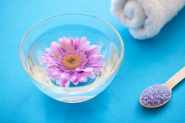 海の塩は木の淡いブルーのぼろぼろのテーブル木のスプーンでひきます、