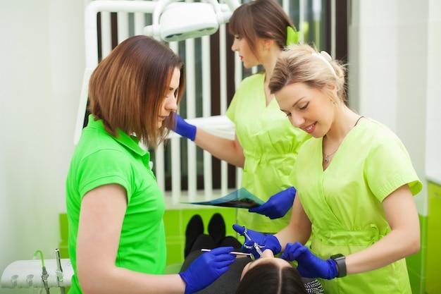 Стоматологи в стоматологическом кабинете разговаривают с пациенткой и готовятся к лечению