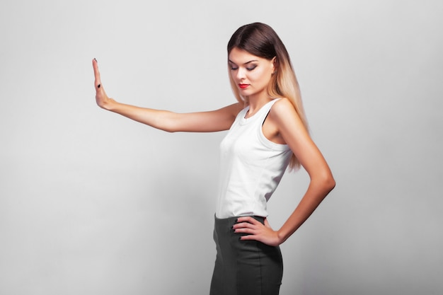 Портрет довольно уверенно вдумчивый девушка, стоя над серой стеной с копией пространства
