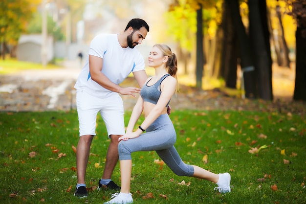 Тренировка женщины с личным тренером в парке