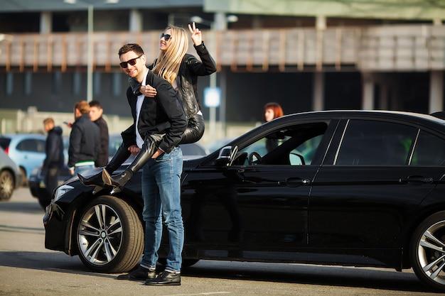 Счастливая молодая пара выбирает и покупает новую машину для семьи