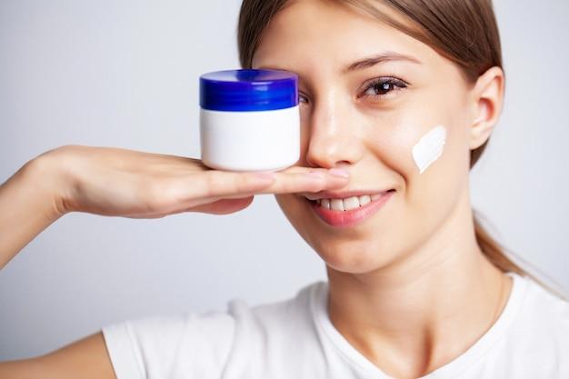 Молодая женщина с красивой кожей наносит на лицо увлажняющий крем