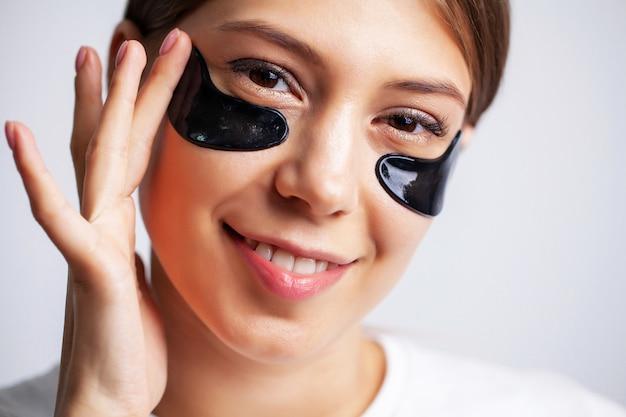 Молодая женщина с красивой кожей наносит черные пятна на лицо