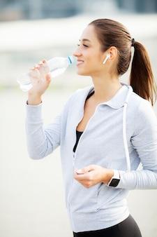 水を飲むヘッドフォンで陽気な女性