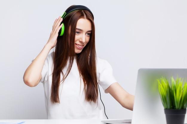 Красивая молодая женщина, слушать музыку в наушниках, работающих на ноутбуке в офисе