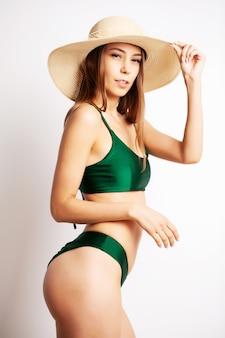 美しい少女は、緑の水着姿で彼女の姿を披露