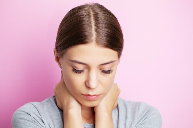 激しい首の痛みに苦しんで疲れた若い女性