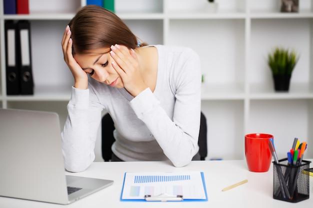 激しい頭痛に苦しんでいるオフィスで疲れきった女性